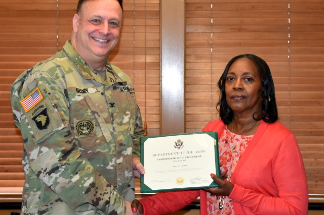 Col. William E. Geesey, USAMMDA commander, presents Teri Glass with a Certificate of Retirement from the Department of the Army.