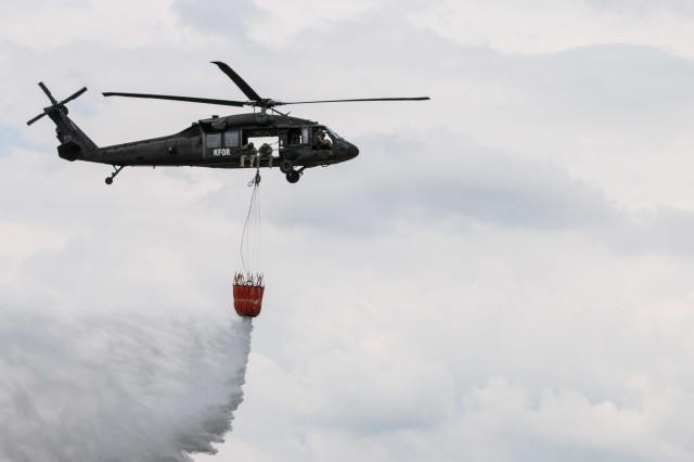 U.S. Army aviation crew members assigned to Multinational Battle Group-East's Southern Command Post drop water from a water bucket attached to a UH-60 Black Hawk Helicopter in Dakovica, Kosovo, May 22. MNBG-East's Southern Command Post conducted water bucket training in order to prepare and support missions of fire suppression and disaster response. (U.S. Army photo by Capt. Rachael Jeffcoat, 20th Public Affairs Detachment)
