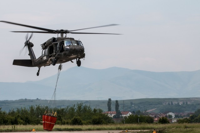 U.S. Army aviation crew members assigned to Multinational Battle Group-East's Southern Command Post hoist a water bucket attached to a UH-60 Black Hawk Helicopter in Dakovica, Kosovo, May 22. MNBG-East's Southern Command Post conducted water bucket training in order to prepare and support missions of fire suppression and disaster response. (U.S. Army photo by Capt. Rachael Jeffcoat, 20th Public Affairs Detachment)