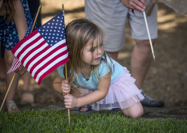 Little girl places American flag