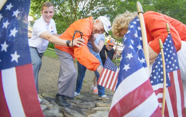 Ben Skardon places a flag on Otis Morgan's stone
