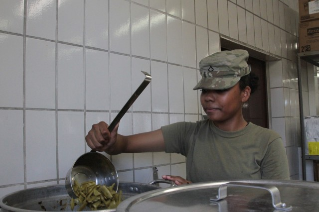 Pfc. Deyonne Robertson, a cook with Company H, 2nd Battalion, 12th Infantry Regiment, 2nd Infantry Brigade Combat Team, 4th Infantry Division stirs a pot of green beans in preparation for supper at Grafenwoehr Training Area, Germany on May 29, 2017. Robertson and her colleagues are constantly supplying all of the Soldiers of the 2-12th with the food they need to continue training overseas. The troops of the 2-12th are participating in an emergency deployment readiness exercise, a part of the Army's readiness initiative to ensure that units can deploy on short notice. (Photo taken by Pvt. Nicholas Vidro, 7th Mobile Public Affairs Detachment.)
