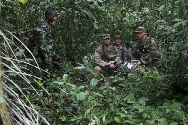 Ghana Armed Forces Sgt. Kofi Francis Donkor observes as U.S. Soldiers assigned to the 1st Battalion, 506th Infantry Regiment, 1st Brigade Combat Team, 101st Airborne Division navigate through the jungle during United Accord 2017 at the Jungle Warfare School on Achiase military base, Akim Oda, Ghana, May 26, 2017. The Jungle Warfare School is a series of situational training exercises designed to train participants in counter-insurgency and internal security operations.