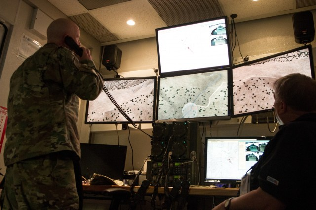 U.S. Army Sgt. 1st Class Brandon Hatchell, a military police platoon sergeant, assigned to Multinational Battle Group- East, communicates with his platoon conducting virtual simulated training on Camp Bondsteel, Kosovo, May 5. The virtual training is part of the Reconfigurable Vehicle Tactical Trailer training, and allows Soldiers to practice a number of simulated scenarios such as convoy operations and range qualifications.