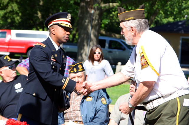 Maj. Lanelle Pickett Jr., headquarters company commandant, U.S. Army Sustainment Command, shakes hands with a Veterans of Foreign Wars Post 143 member, George Rose, before a Memorial Day ceremony in Orion, Illinois, May 29.