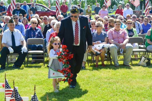 Gary Berndt, post commander, American Legion Post 711, accompanies a child as she lays flowers at a memorial for the fallen during a Memorial Day service at Blue Grass Cemetery in Blue Grass, Iowa, May 29.