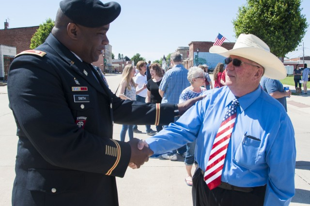 Lt. Col. Rodney Smith from the U.S. Army Sustainment Command shakes the hand of David Dobbels, vice president of the Cambridge Rotary Club, following a Memorial Day remembrance ceremony at the Cambridge Community Hall in the Village of Cambridge, Illinois, May 29.