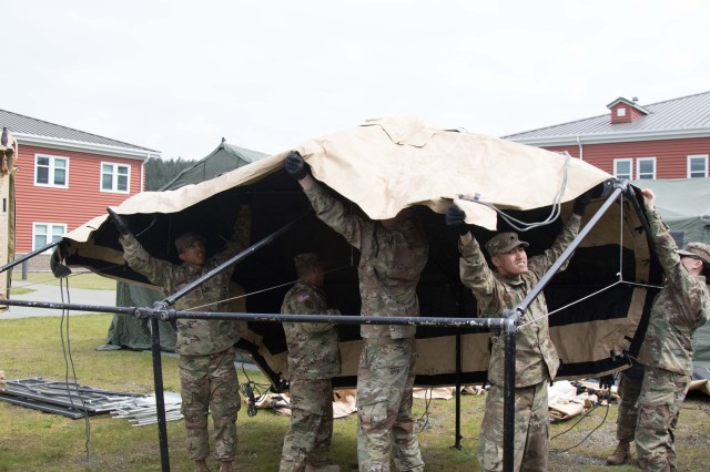 Soldiers of 17th Field Artillery Brigade place the roof piece onto the tent skeleton at Joint Base Lewis-McChord, Wa., May 17, 2017. The 17th FA Bde. conducts a Command Post exercise to ensure that they are ready to deploy and fight quickly.