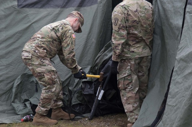 A 17th Field Artillery soldier hammers a stake into the ground to secure the tents at Joint Base Lewis-McChord, Wa., May 17, 2017. The 17th FA Bde. conducts a Command Post exercise to ensure that they are ready to deploy and fight quickly.