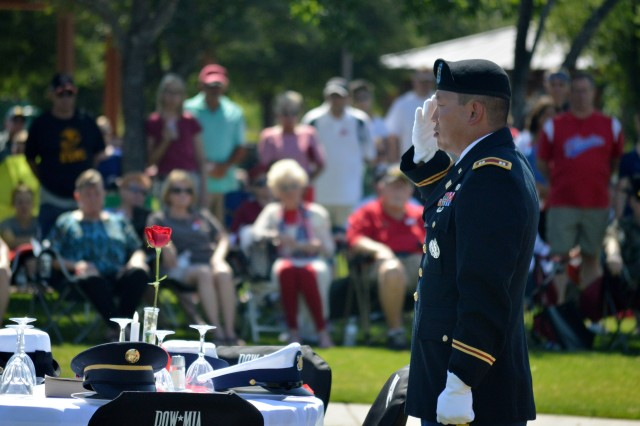 Capt. Matthew Peterson, commander, Phoenix North Recruiting Company, Phoenix Recruiting Battalion, salutes at the table of the Missing in Action and Prisoners of War, during the Anthem Memorial Day Ceremony, May 29, Veterans Memorial, Anthem, Ariz. (Photo by Alun Thomas, USAREC Public Affairs)