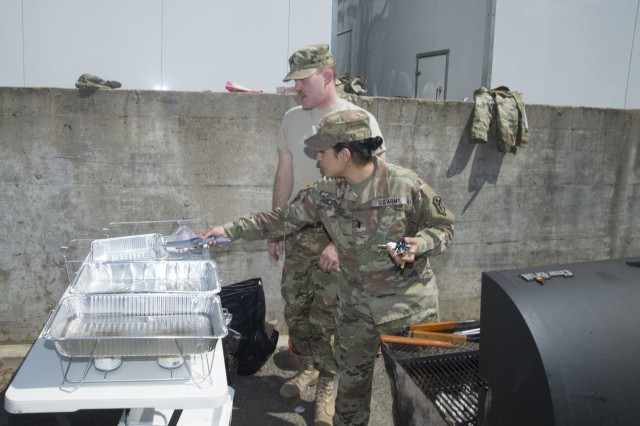 1st Lt. Jenny Carlo (front), executive officer, Headquarters and Headquarters Company (HHC), U.S. Army Intelligence and Security Command (INSCOM), and Sgt. Chad Harrell, HHC systems maintainer, ready the grill in preparation for an Army Emergency Relief fund food service event at the Nolan Building on Fort Belvoir, Virginia, April 13.