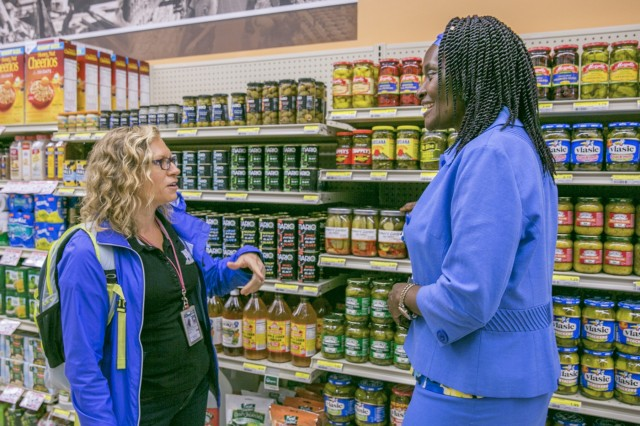 Noelle Austin-Jones, Army Wellness Center health technician, left, speaks with Velma Siler, commissary officer at Sagamihara Family Housing Area, right, about the commissary's health-focused products during the Healthy Lifestyles event held May 26, 2017 at SFHA Commissary. (U.S. Army photo by Honey Nixon)