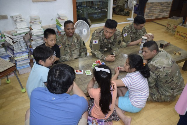 U.S. Soldiers and Korean Augmentees to the United States Army assigned to 35th Air Defense Artillery Brigade, and children from the Pyeongtaek Local Children's Center, play a competitive game of cards at the Pyeongtaek Local Children's Center May 30, 2017 during a community outreach event.