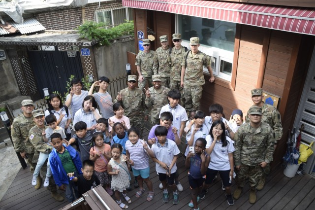 U.S. Soldiers and Korean Augmentees to the United States Army assigned to 35th Air Defense Artillery Brigade, and children and staff of the Pyeongtaek Local Children's Center, take a photo May 30, 2017 during community outreach event.