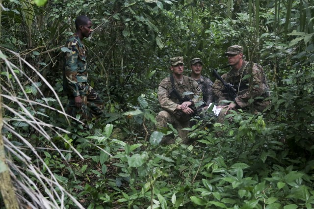 Ghana Armed Forces Sgt. Kofi Francis Donkor observes as U.S. Soldiers assigned to the 1st Battalion, 506th Infantry Regiment, 1st Brigade Combat Team, 101st Airborne Division navigate through the jungle during United Accord 2017 at the Jungle Warfare School on Achiase military base, Akim Oda, Ghana, May 26, 2017. The Jungle Warfare School is a series of situational training exercises designed to train participants in counter-insurgency and internal security operations. (U.S. Army photo by Sgt. Brian Chaney)