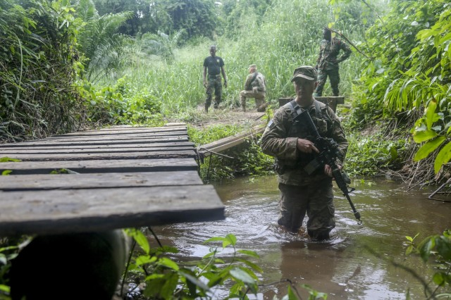 U.S. Army Spc. Jake Burley assigned to the 1st Battalion, 506th Infantry Regiment, 1st, Brigade Combat Team, 101st Airborne Division maneuvers through a river during United Accord 2017 at the Jungle Warfare School on Achiase military base, Akim Oda, Ghana, May 26, 2017. The Jungle Warfare School is a series of situational training exercises designed to train participants in counter-insurgency and internal security operations. (U.S. Army photo by Sgt. Brian Chaney)
