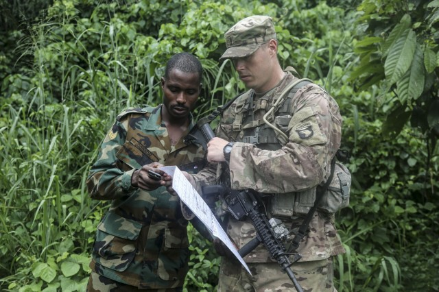 Ghana Armed Forces Sgt. Kofi Francis Donkor reviews his position on a map with U.S. Army 2nd Lt. Hugh Smith assigned to the 1st Battalion, 506th Infantry Regiment, 1st Brigade Combat Team, 101st Airborne Division during United Accord 2017 at the Jungle Warfare School on Achiase military base, Akim Oda, Ghana, May 26, 2017. The Jungle Warfare School is a series of situational training exercises designed to train participants in counter-insurgency and internal security operations. (U.S. Army photo by Sgt. Brian Chaney)