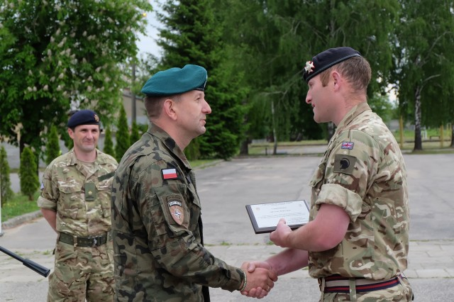 Polish 15th Mechanized Brigade General Jaroslaw Gromadzinski presents an award to Battle Group Poland's Cpl. Scott Mallen, 1st Troop, A Squadron, The Light Dragoons, for his heroic, real-life action in fighting a house fire which occurred in Ruda, Poland, while the battle group was participating in joint training exercise Puma17 May 24. (U.S. Army photo by Spc. Kevin Wang/Released)