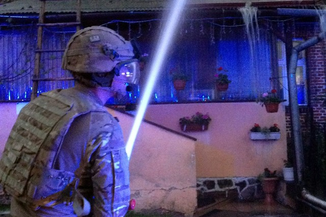 Cpl. Scott Mallen hoses down the roof of a house to put out flames. Mallen and other Battle Group Poland soldiers from 1st Troop, A Squadron, The Light Dragoons took a pause from their training exercise Puma17 to help fight a nearby house fire in Ruda May 24.