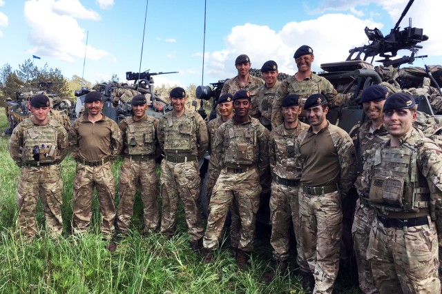 Battle Group Poland's soldiers from 1st Troop, A Squadron, The Light Dragoons, pose for photos during joint training exercise Puma17. The Light Dragoons took a pause from their training exercise to help fight a nearby house fire in Ruda, Poland May 24.