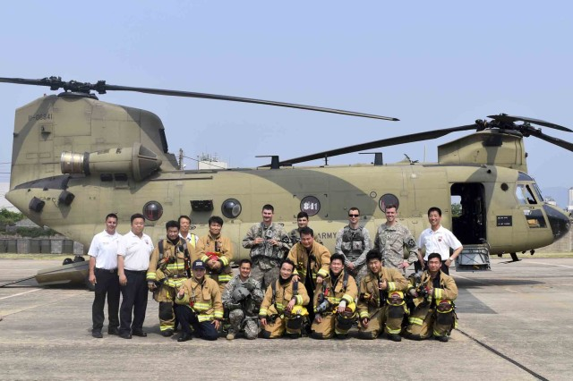 Firefighters from USAG Daegu Fire & Emergency Services and U.S. Soldiers pose for a group photo in front of the CH-47 Chinook after the CH-47 Egress Training, May 31, 2017. Firefighters respond to the crash scene and take action to mitigate hazards, rescue and triage the injured and take proper care of the patients.