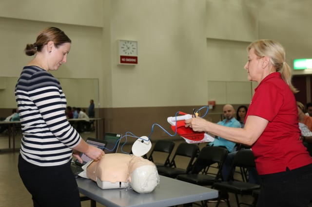Laura Brookins, left, and Donna Butler, right, volunteer and station manager respectively for Camp Zama's American Red Cross, demonstrate how to use an automated external defibrillator to employees for U.S. Army Corps of Engineers Japan District's safety day held June 2  inside Camp Zama's Community Recreation Center. (U.S. Army photo by Noriko Kudo)