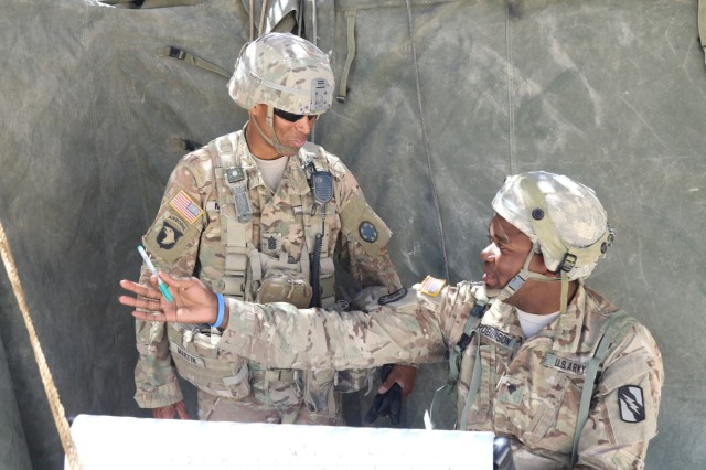 Command Sgt. Maj. Jon A. Martin, an observer controller at the National Training Center, speaks with Spc. Cory Robinson, assigned to Headquarters Company, 150th Engineer Battalion, Mississippi Army National Guard, about his training experience during his rotation, June 2, 2017, at the National Training Center.