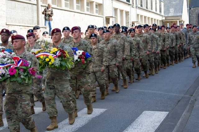 """Berets and wreaths. MONTEBOURG, France--More than 100 U.S. Army Soldiers, join the commanding general, French compatriots and people of Montebourg, France, during a march from the town center to the town's World War II memorial wall. Select Soldiers from """"Fighting Eagles,"""" 1st Battalion, 8th Infantry Regiment of the 3rd Armored Brigade Combat Team, 4th Inf. Div., participated in the march to the memorial dedication hosted by Maj. Gen. Ryan F. Gonsalves, commanding general of the 4th Inf. Div., Monteburg civic leaders, French compatriots and veterans. The Soldiers of 3rd ABCT are currently deployed in support of Operation Atlantic Resolve, U.S. forces' commitment to the collective security of eastern Europe, conducting bilateral training and multinational exercises with NATO Allies and Partners. The last time the 1st Bn., 8th Inf. Regt. deployed to Europe the Fighting Eagle Soldiers landed at Utah Beach with the Assault Division on D-Day in 1944. The 1st Bn., 8th Inf. Regt., currently stationed in Romania, sent Soldiers who had recently earned the Expert Infantryman's Badge during testing earlier this year. The Soldiers served as guests of honor at the ceremony, where Gonsalves and community leaders laid wreaths at the memorial.  (U.S. Army photo by Maj. Anthony Clas, 7MPAD)"""