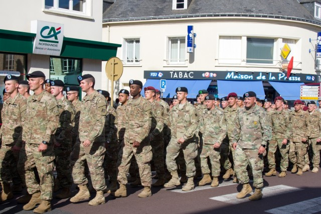 """Get in Step. MONTEBOURG, France--First Sgt. Ronald Colon, center, first sergeant, Battery A, 3rd Battalion, 29th Field Artillery Regiment, attached to the 1st Battalion, 8th Infantry Regiment, 3rd Armored Brigade Combat Team, 4th Infantry Division, marches more than 100 U.S. Army Soldiers through downtown Montebourg, France, following a ceremony honoring the 4th Inf. Div.'s role in the liberation of Normandy, June 3, 2017. Ramirez and the """"Fighting Eagles"""" Soldiers of 3rd ABCT, attended a dedication ceremony for a memorial in the town's center with Maj. Gen. Ryan F. Gonsalves, commanding general of the 4th Inf. Div., to commemorate the 73rd anniversary of the 4th Inf. Div.'s assault at Utah Beach and the following liberation of Montebourg. Select Soldiers from 1st Bn., 8th Inf. Regt., 3rd ABCT, 4th Inf. Div., participated in the march, the dedication ceremony at Montebourg's World War II memorial, and dinner hosted by township's civic leaders. The Soldiers of 3rd ABCT are currently deployed in support of Operation Atlantic Resolve, U.S. forces' commitment to the collective security of eastern Europe conducting bilateral training and multinational exercises with NATO Allies and Partners. The Soldiers were guests of honor at the ceremony, where Gonsalves and community leaders laid wreaths at the memorial.  (U.S. Army photo by Master Sgt. Brent M. Williams, MCE Public Affairs, 4th Inf. Div.)"""