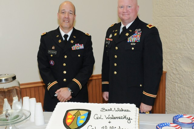 Col. Paul Walenesky and Col. Eric Holliday pose by their cake, following the official Retirement Ceremony for both officers, held at the Rock Island Arsenal, June 2.