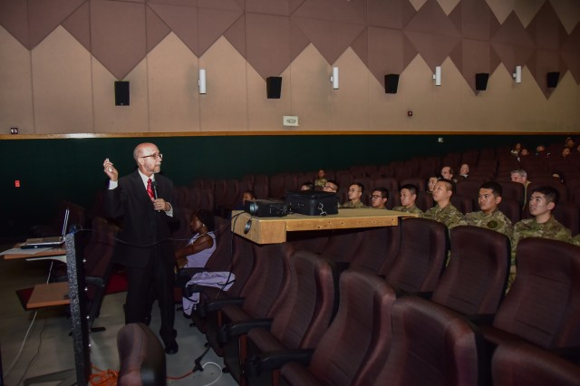Russell Strand, a retired U.S. Army CID Special Agent with an excess of 38 year's law enforcement, investigative, and consultation experience shows the audience a short clip of Army recruiting advertisements that screened 20 years ago, May 30 at Yongsan MPTF.