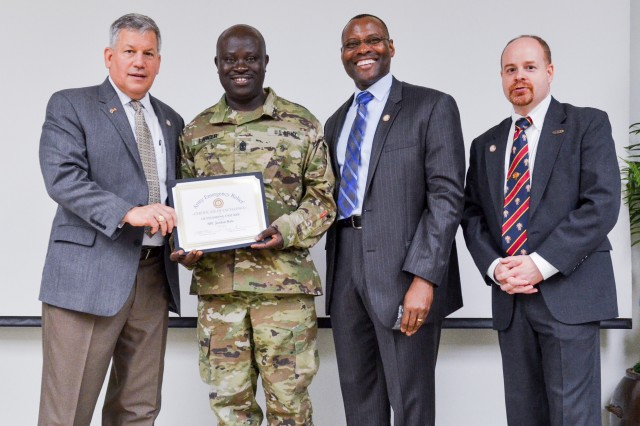 Retired Lt. Gen. Raymond V. Mason, Army Emergency Relief program director presents an Outstanding Unit Representative award to 1st Sgt. Emmanuel Lawer, Headquarters and Headquarters Company, U.S. Army Garrison Yongsan first sergeant May 24, after he was able to increase his unit's donations by over 1,000 percent from the previous year. The first sergeant is flanked also by Command Sgt. Maj. (Ret.) Charles Durr, AER Financial Assistance, and Ryan Ritter, AER Officer Yongsan Army Community Service.