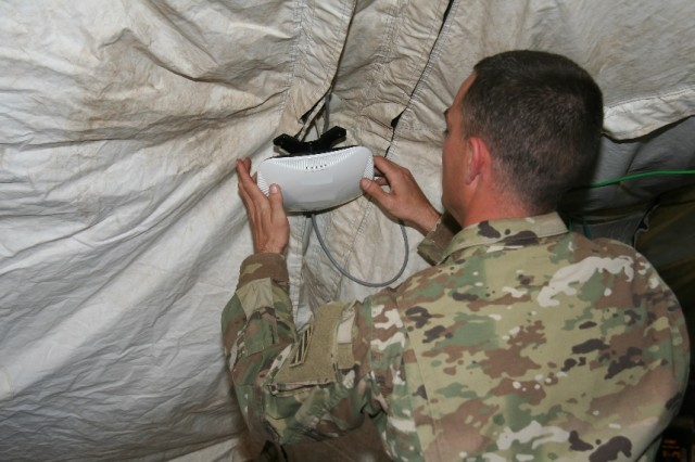 A Soldier from the 1st Armored Brigade Combat Team, 3rd Infantry Division (1/3 ID) sets up a Secure Wireless Access Point in the brigade main command post as part of a pilot of the capability during the unit's training rotation at the National Training Center, at Fort Irwin, California, in April 2017.