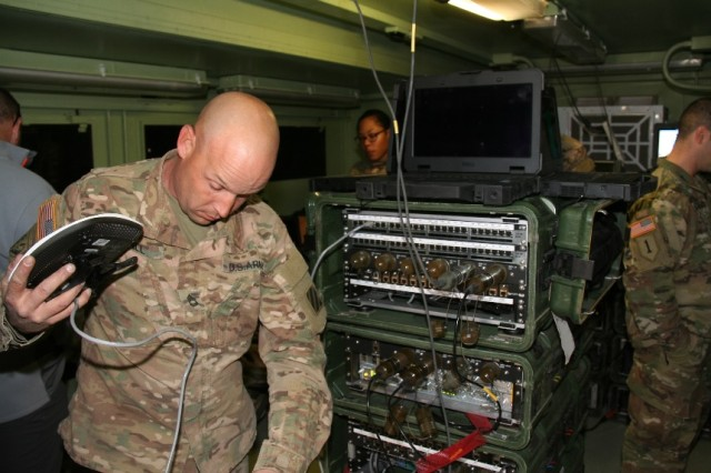 A Soldier from the 1st Armored Brigade Combat Team, 3rd Infantry Division (1/3 ID) sets up a Secure Wi-Fi Access Point in the network operations center that supports the brigade main command post, as part of a Secure Wireless pilot during the unit's training rotation at the National Training Center, at Fort Irwin, California, in April 2017. The Secure Wi-Fi network stack is to his right.  (U.S. Army photo by Amy Walker, PEO C3T Public Affairs)