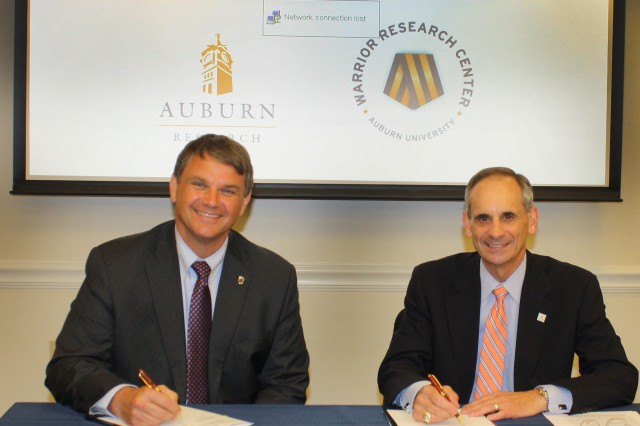 AMRDEC Acting Director Jeff Langhout signs the cooperative research and development agreement with Dr. John Mason, Auburn's vice president for research and economic development.