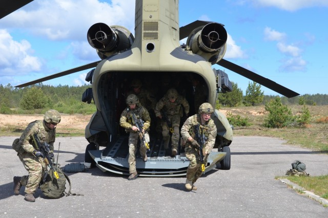 ADAZI MILITARY BASE, Latvia - U.K.'s Royal Marine Commandos rush out of the CH-47 Chinook in a session of cold load training, helicopter pads, Adazi, June 2.  Cold load training is the practice of entering or exiting the aircraft while the aircraft is shut down.  The training and the aircraft is provided by 10th Combat Aviation Brigade Soldiers currently in Lielvarde, Latvia.  The training is to prepare for an upcoming event during Exercise Saber Strike, which will include the quick uploading and offloading of personnel.  Saber Strike is a U.S. Army Europe-led multinational combined forces training exercise in the Baltic region.  The exercise tests the capability of multiple nations to act against a threat.  (U.S. Army photo by Sgt. Shiloh Capers)