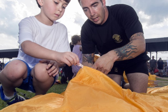 Wilson Black, 6, helps Staff Sgt. Kenneth Severin pack his parachute following a demonstration by the Golden Knights Parachute Team.