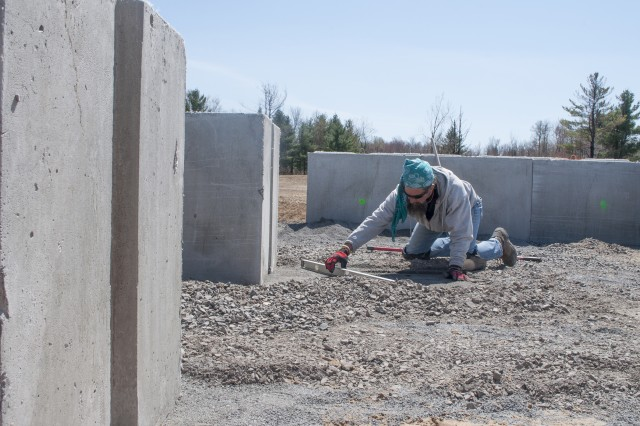 Electronics worker Dave Hewitt smooths stone inside a shock-absorbing concrete building under construction at Range 24.