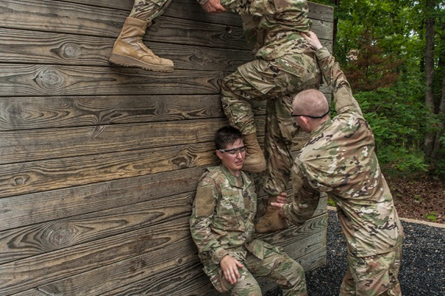 Soldiers in training with Company A, 2nd Battalion, 10th Infantry Regiment, use teamwork to navigate an obstacle on the confidence course as part of a six-week Basic Combat Training cycle for prior-service Soldiers.