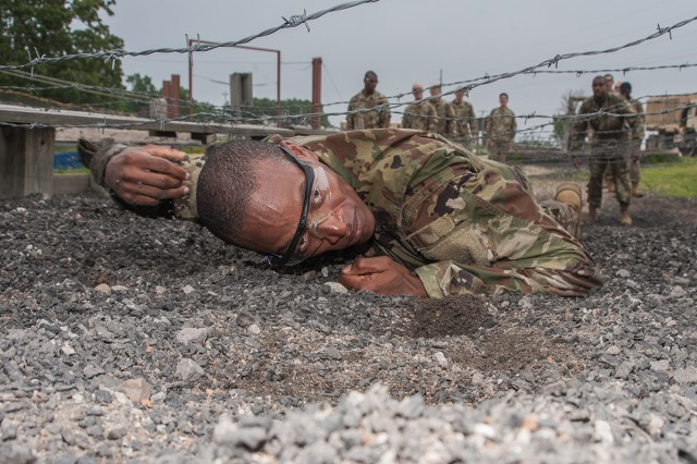 Pfc. Michael Williams, Company A, 2nd Battalion, 10th Infantry Regiment, low crawls under a barbed-wire obstacle at the confidence course as part of a six-week Basic Combat Training cycle for prior-service Soldiers. Williams, who served in the U.S. Navy from 2008 to 2014, is one of 32 prior-service Soldiers conducting training with Co. A.