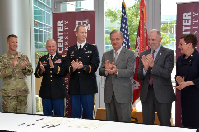 Officials from both Fort Hood and Texas A&M officials applaud Carl R. Darnall Army Medical Center and Texas A&M's new partnership that will provide clinical rotation opportunities to medical students in the Fort Hood hospital.  From left, Col. Todd Fox, Fort Hood Garrison commander; Col. Mark Thompson, CRDAMC commander; Col. James Lucas, CRDAMC's deputy commander for surgical services and program's dean;  John Sharp, Texas A&M University System chancellor; Michael K. Young, Texas A&M University president; and Carrie L. Byington, MD, Texas A&M College of Medicine dean, Texas A&M University Health Science Center senior vice president and the university's health services vice chancellor.
