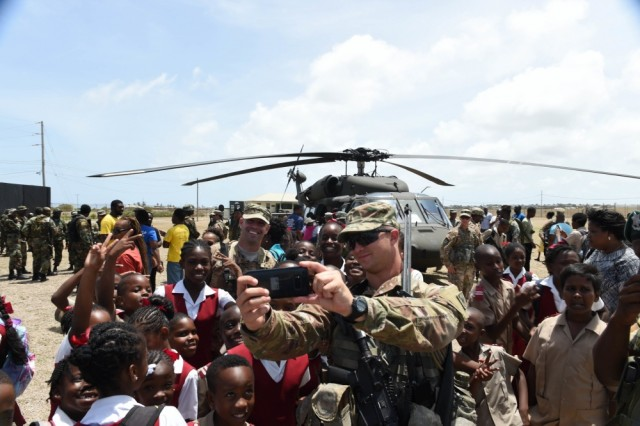 Florida Army National Guard 2nd lt. Ryan Noblitt, assigned to Delta Company, 1-124 Infantry, 53rd Brigade Combat Team, takes a selfie with local schoolchildren and another soldier in his unit, Staff Sgt. Edward Roseman during a community relations (COMREL) event on board Paragon Base. The students visited the base to participate in a Tradewinds 2017 COMREL event that allowed local school children to meet with members of the armed forces from multiple participating countries, ask them questions, and check out their equipment up close. Tradewinds is a joint, combined exercise conducted in conjunction with partner nations to enhance the collective abilities of defense forces and constabularies to counter transnational organized crime, and to conduct humanitarian/disaster relief operations.