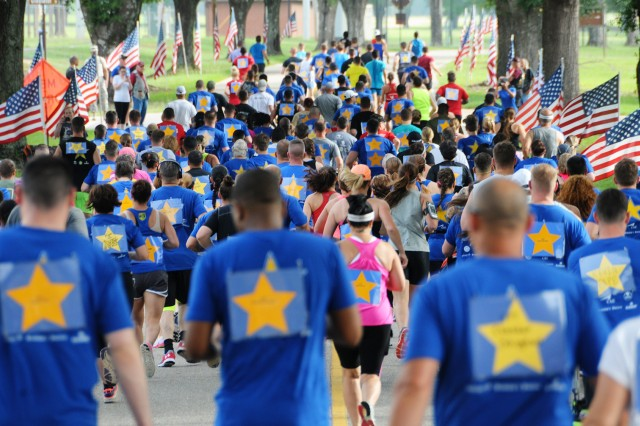 Runners clad with gold stars representing fallen service members make their way through the course during the Survivors and Fallen Heroes 5k run June 3 at the Fort Rucker Physical Fitness Center.