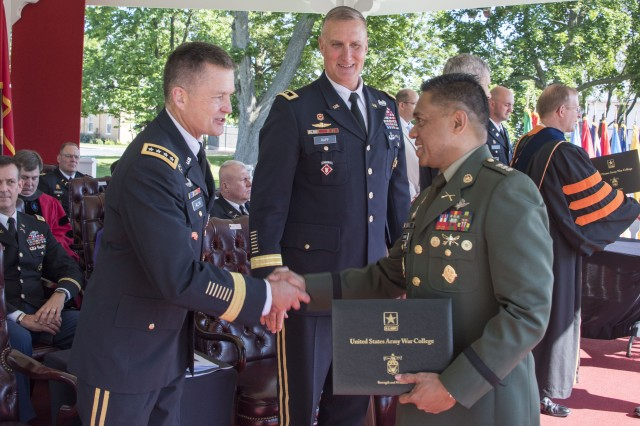 Col. Romeo S. Brawner of the Philippines accepts his Army War College diploma and congratulations from Gen. Dan Allyn, Vice Chief of Staff of the Army, Jun