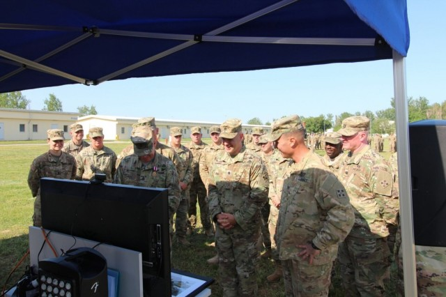 """Lt. Col. Jason Sabat (center), outgoing commander of 1st Battalion, 8th Infantry Regiment, 3rd Armored Brigade Combat Team, 4th Infantry Division, and Cmd. Sgt. Maj. Jay Morse (front left), outgoing battalion command sergeant major, greet their families back at home station Fort Carson, Colorado, via teleconference prior to their combined change of command and responsibility ceremony at Mihail Kogalniceanu Air Base, Romania, June 5, 2017. The two men, who led 3/4 ABCT's """"Task Force 1-8 Infantry"""" as the southern rotational land force for Operation Atlantic Resolve, passed the command team torch to Lt. Col. Mark Battjes and Cmd. Sgt. Maj. Timothy Chrysler. (U.S. Army photo by 1st Lt. Samuel Jolley, 3rd Armored Brigade Combat Team, 4th Infantry Division)"""