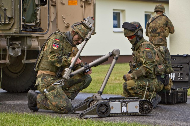 OR Daniel Eisenreich, explosive ordinance exposal specialist, and OR Steven Madison, EOD specialist in training, both assigned to 3rd Company, 4th Panzer Pioneer Battalion, 15th Panzer Brigade, German Army, prepare the PackBot Multi-mission Tactical Robot for a mission during a class on Camp Aachen, Grafenwoehr Training Area, Germany June 7, 2017. The German Soldiers participated in an explosive hazards search, detection, identification, and defeat training in order to gain proficiency on explosive hazard clearing operations with Bravo Troop, Regimental Engineer Squadron, 2d Cavalry Regiment, U.S. Army.