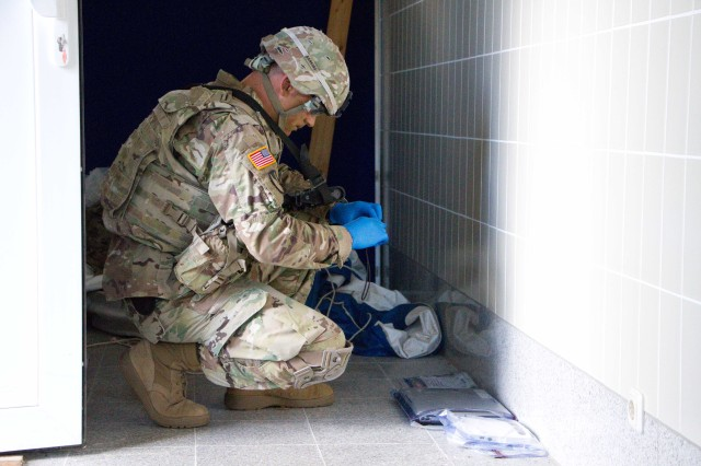 Staff Sgt. Andrew Nee, a combat engineer assigned to Bravo Troop, Regimental Engineer Squadron, 2d Cavalry Regiment, U.S. Army takes photos of evidence during training on Camp Aachen, Grafenwoehr Training Area, Germany June 7, 2017. Bravo Troop Soldiers participated in an explosive hazards search, detection, identification, and defeat training in order to gain proficiency on explosive hazard clearing operations with 3rd Company, 4th Panzer Pioneer Battalion, 15th Panzer Brigade, German Army.