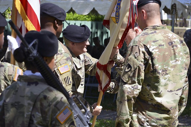 Col. Tony McQueen, outgoing commander of the 402nd Army Field Support Brigade, returns the unit colors to Maj. Gen. Ed Daly, formally relinquishing command. (Photo by Capt. Lonnie Collier, ASC Public Affairs)