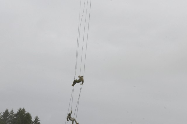 Soldiers and Airmen rappel out of a UH-60 Black Hawk helicopter during the Air Assault course held at Camp Rilea in Warrenton, Oregon, June 8, 2017. Rappelling is one of the tests service members must complete to be awarded the Air Assault badge. The course consists of physical training, ruck marches, classroom instruction, and hands-on practical exercises.