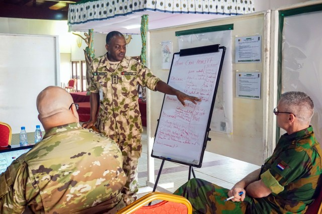 A Nigerian military officer briefs his working group during discussions at Exercise Unified Focus 2017, held at the Douala Naval Base, Cameroon, April 26, 2017. UF 17 is a weeklong tabletop exercise that brings the military partners of the Lake Chad basin area's Multinational Joint Task Force (MNJTF) together to practice joint planning and coordination through a series of scripted vignettes.